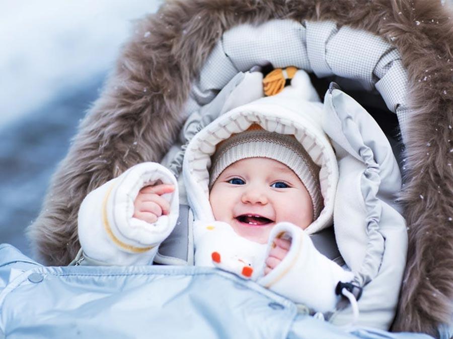 smejúce sa bábätko v kočíku v zime