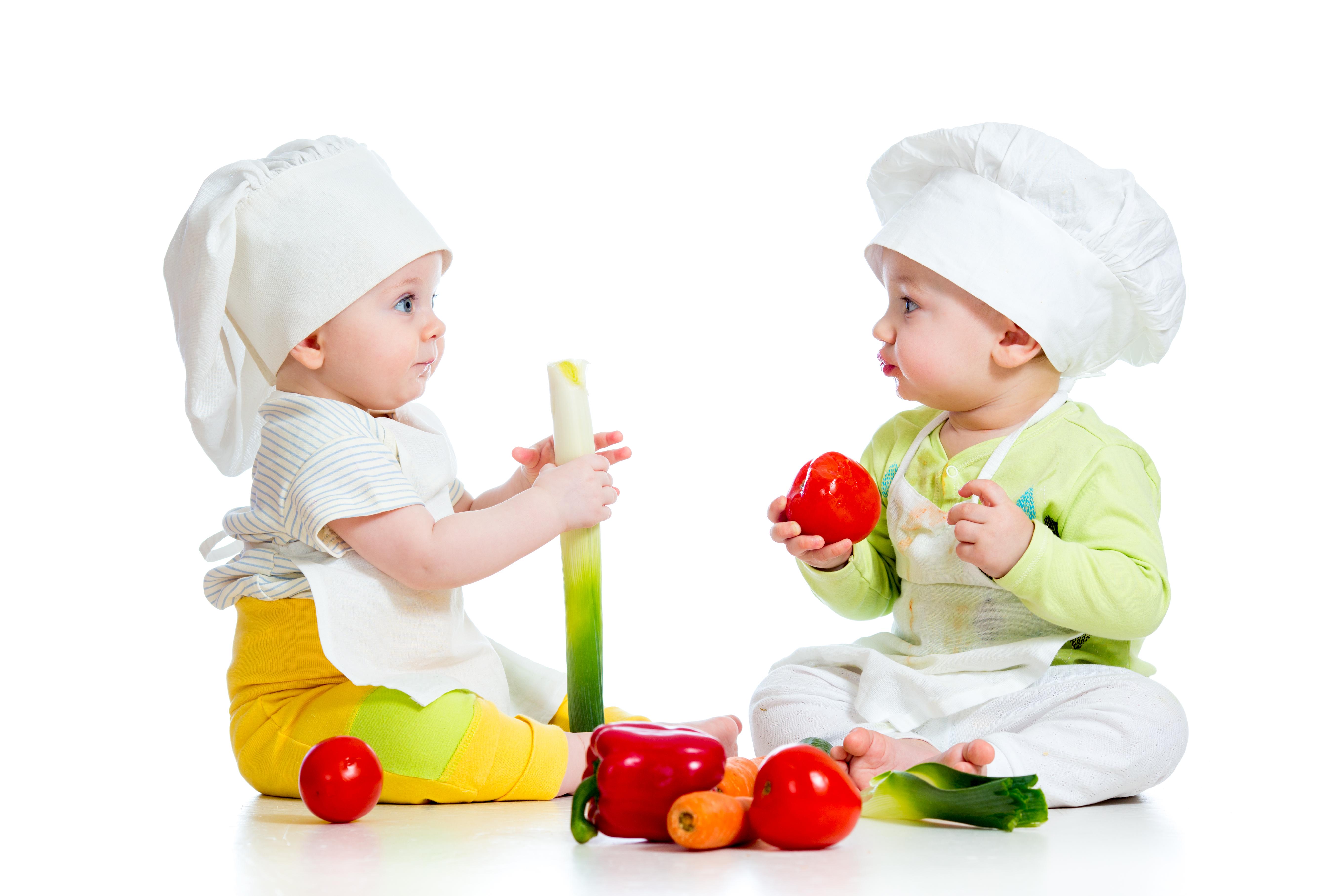 dve deti s kuchárskymi čiapkami na hlave jedia zdravú zeleninu