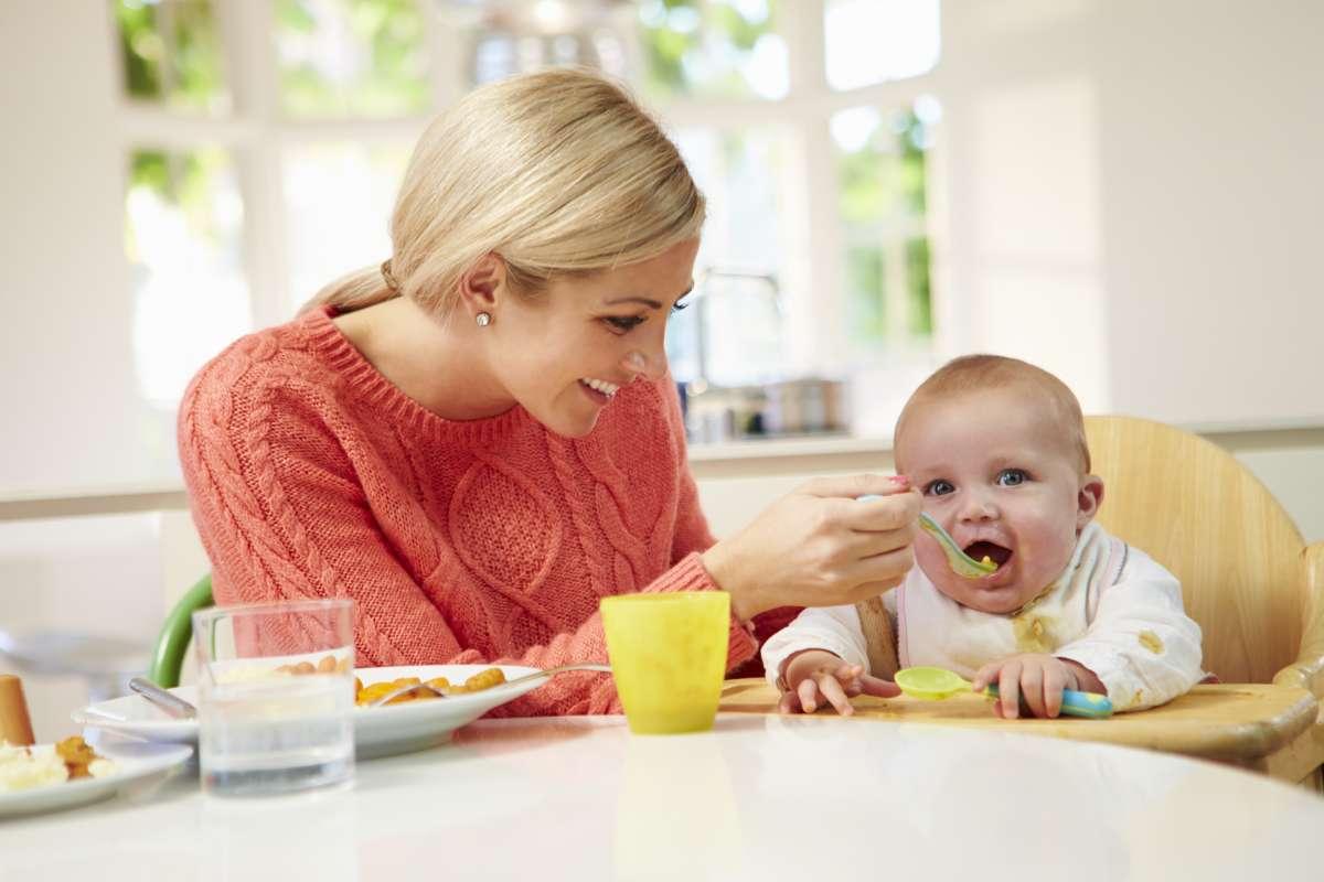 mama kŕmi dieťa na jedálenskej stoličke