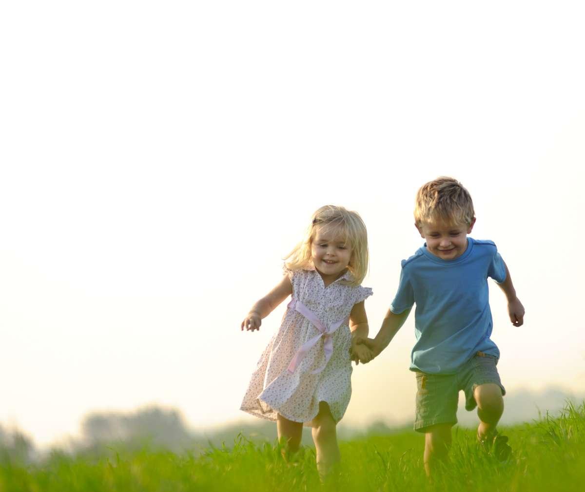 chlapček a dievčatko bežia po zelenej lúke držiac sa za ruky