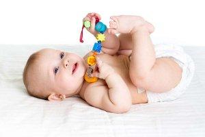 dieťatko ležiace na bielej podložke drží hračku
