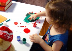 dievčatko roztiera prstami farbu po papieri